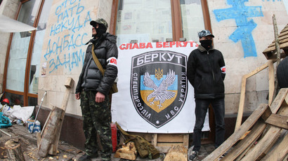 "Anti-government activists stand in front of a placard bearing the logo of Ukraine's disbanded elite Berkut riot police and reading ""Glory to Berkut"" as they guard a barricade outside a regional state building in the eastern Ukrainian city of Donetsk on April 14, 2014. (AFP Photo / Alexander Khudoteply)"