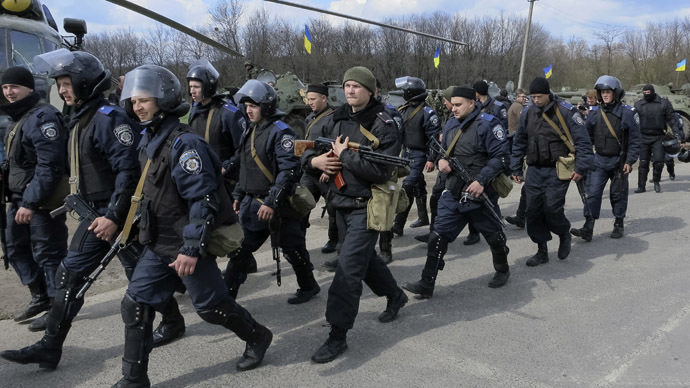 Members of the Ukrainian Interior Ministry walk past a MI-8 military helicopter and armored personnel carriers at a checkpoint near the town of Izium, eastern Ukraine, April 15, 2014. (Reuters / Dmitry Madorsky)