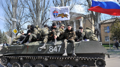 "Men wearing military fatigues sit by a Russian flag and a white flag reading ""People's volunteer corps of Donetsk"" as they ride on an armoured personnel carrier (APC) in the eastern Ukrainian city of Slavyansk on April 16, 2014. (AFP Photo)"