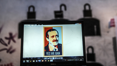 "A view of a computer screen showing a digital portrait of the Turkish Prime Minister and text reading ""Yes we ban"" on a laptop computer screen, in front of graffiti in Istanbul (AFP Photo / Ozan Kose)"