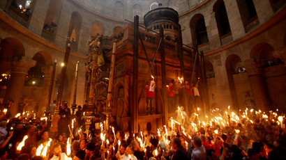 Christian Orthodox worshippers hold up candles lit from the 'Holy Fire' as thousands gather in the Church of the Holy Sepulchre in Jerusalem's old city on April 19, 2014 during the 'Holy Fire' ceremony on the eve of the Orthodox Easter (AFP Photo / Gali Tibbon)