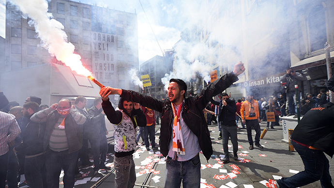 Galatasaray, Fenerbahce and Besiktas fan groups use flares as they protest against a new system of e-tickets on April 20, 2014, on Istiklal Avenue in Istanbul. (AFP Photo / Bulent Kilic)