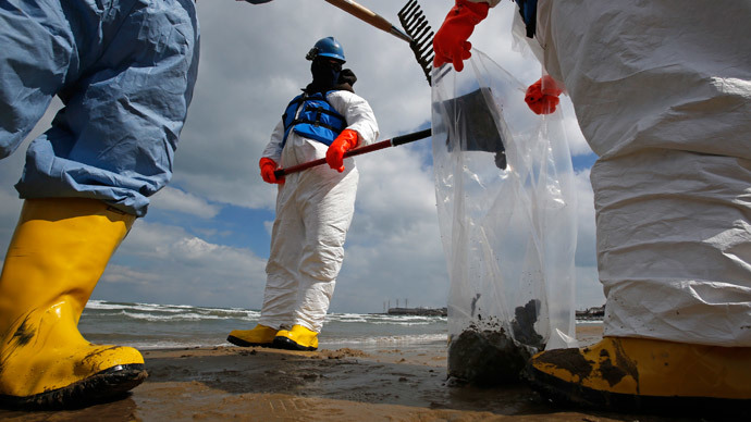 Oil spill response contractors clean up crude oil on a beach after a BP oil spill on Lake Michigan in Whiting, Indiana March 25, 2014.(Reuters / Jim Young)