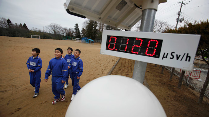 Students walk near a geiger counter, measuring a radiation level of 0.12 microsievert per hour, at Omika Elementary School, located about 21 km (13 miles) from the tsunami-crippled Fukushima Daiichi nuclear power plant, in Minamisoma, Fukushima prefec