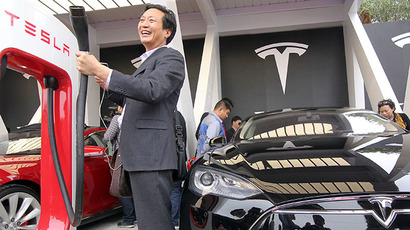 "A Chinese guest poses for a photo by a Tesla ""supercharger"" on a car handover ceremony in Shanghai as American electric carmaker Tesla Motors delivers their Model S cars to its first buyers in China on April 23, 2014. (AFP Photo)"
