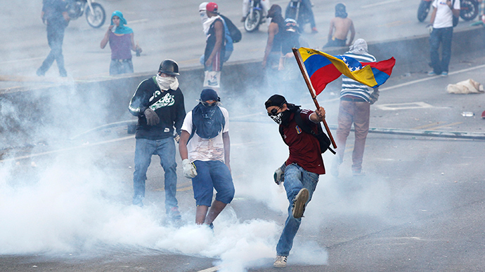 An anti-government protester, with the Venezuelan flag, kicks back a gas canister to police during a demonstration in which masked youths battled police and blocked a main highway in Caracas April 21, 2014 (Reuters / Christian Veron)