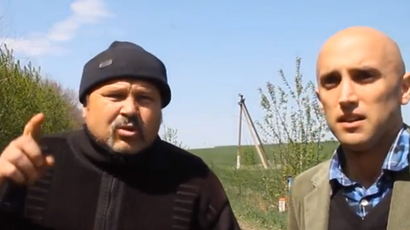 Local activist (L) speaks about Ukrainian army attack at a checkpoint near Slavyansk (A still from RT video)
