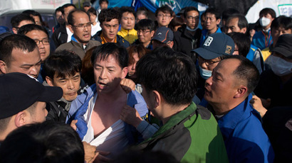 "Relatives of victims of the ""Sewol"" ferry express their frustrations as they surround deputy head of the national coastguard Choi Sang-Hwan (C) after forcibly removing him from an office at Jindo harbour on April 24, 2014. (AFP Photo/Ed Jones)"