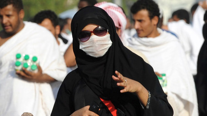 A Muslim pilgrim wears a mask due to fears linked to the MERS virus, as she heads to noon prayers at the Namira mosque, near Mount Arafat (AFP Photo)