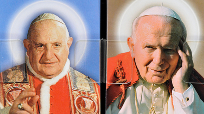 This picture taken on April 21, 2014 shows postcards depicting Pope John XXIII (L) and Pope John Paul II sold in a shop in central Rome. (AFP Photo / Tiziana Fabi)