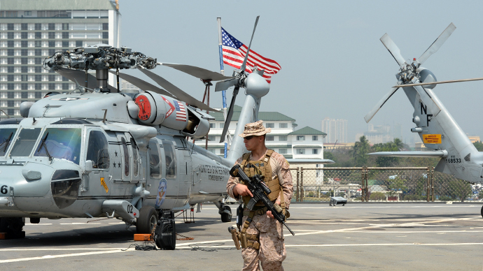 An armed US marine patrols next to seahawk helicopters on the deck of 7th Fleet command ship, USS Blue Ridge shortly after arriving at the international port in Manila on March 18, 2014, for a port visit. (AFP Photo / Ted Aljibe)