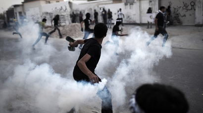 A Bahraini protestor throws a tear gas canister back at riot police during clashes following a protest condemning the death of Ahmed Al-Mosajen and Ali Abbas, in the village of Al-Maqsha, west of Manama, on April 25, 2014. (AFP Photo / Mohammed Al-Shaikh)