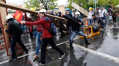 A protester uses a slingshot while others take cover during a May Day demonstration in Istanbul May 1, 2014 (Reuters / Umit Bektas)