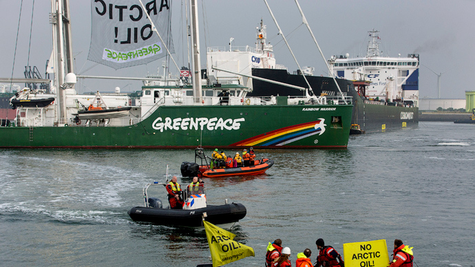 """Greenpeace ship, the Rainbow Warrior, passes Russian oil tanker Mikhail Ulyanov after members of Greenpeace draped banners saying """"No Arctic Oil"""" from it, in the harbour of Rotterdam May 1, 2014 (Reuters / Michael Kooren)"""