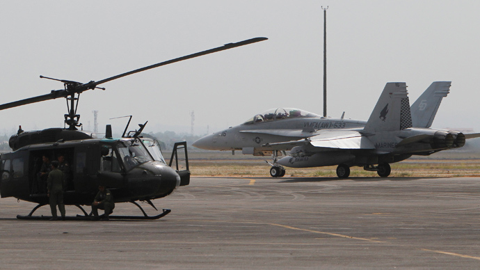 A U.S. Marine Corps F/A-18 Hornet jet fighter taxis past a Huey helicopter at the formerly U.S. bases, Clark Air Base, Pampanga province, north of Manila (Reuters / Romeo Ranoco)