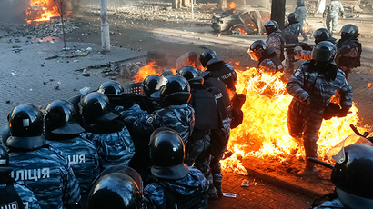 Riot policemen stand guard as they are hit by fire caused by molotov cocktails hurled by anti-government protesters during clashes in Kiev February 18, 2014 (Reuters / Stringer)