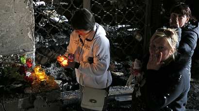 A woman lights a candle in memory of people killed in recent street battles between pro-Russian and pro-Ukrainian supporters inside a trade union building in the Black Sea port of Odessa May 4, 2014. (Reuters / Gleb Garanich)