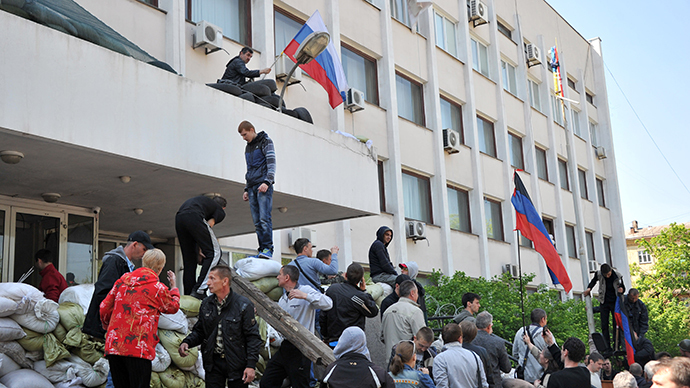 An activist sets Russian flag on the state city building in southern Ukrainian city of Mariupol after Ukrainian policemen left guarding the building on May 7, 2014. (AFP Photo / Genya Savilov)