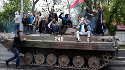 People ride on a towed armored vehicle captured after Ukrainian forces attacked police headquarters in Mariupol May 9, 2014.(Reuters / Marko Djurica)