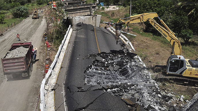 An excavator-mounted hydraulic jackhammer is being used to break up the concrete of the collapsed bridge Cuajilote after an earthquake struck the area in Tecpan de Galeana May 9, 2014. (Reuters / Claudio Vargas)