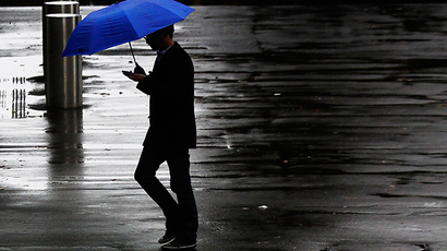 A pedestrian crosses a street on a rainy day in central Sydney (Reuters / Daniel Munoz)