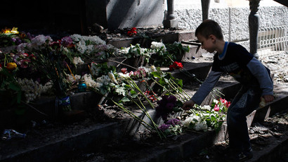 A boy places flowers in front of a gutted police station building in Mariupol, eastern Ukraine May 10, 2014.(Reuters / Marko Djurica)