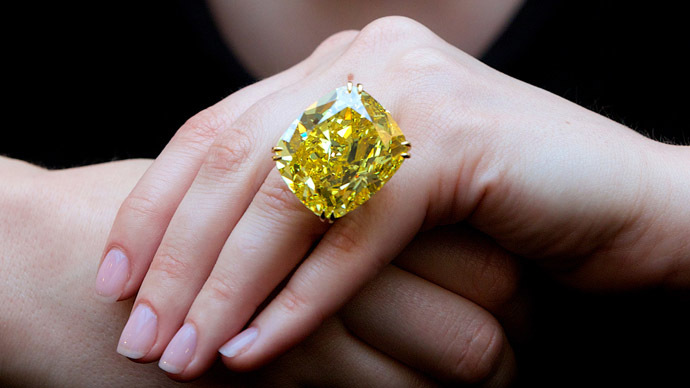 "A Sotheby's employee poses for pictures with the ""Graff Vivid Yellow,"" at 100.09 carats, one of the rarest yellow diamonds of its size, in London on April 11, 2014. (AFP Photo/Andrew Cowie)"