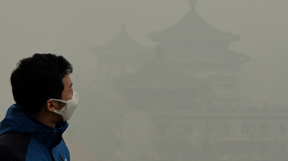 A tourist wearing a face mask climbs Jingshan Hill beside the Forbidden City as heavy air pollution continues to shroud Beijing on February 26, 2014. (AFP Photo/Mark Ralston)