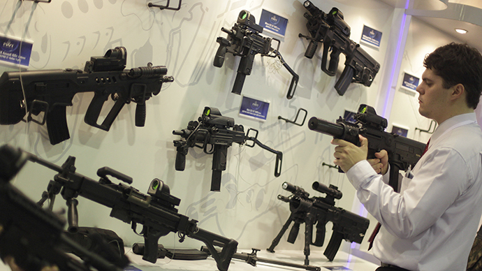 A man looks at a sub machine gun displayed at the Latin America Aero and Defence trade show (Reuters / Ricardo Moraes)