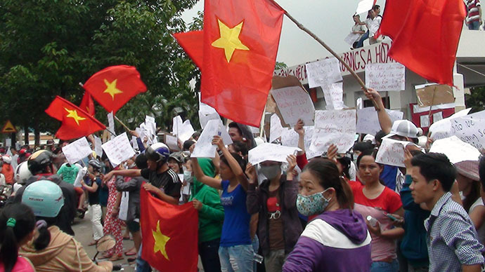 Protesters wave flags and hold placards on a street outside a factory building in Binh Duong on May 14, 2014, as anti-China protesters set more than a dozen factories on fire in Vietnam. (AFP Photo / VNExpress)