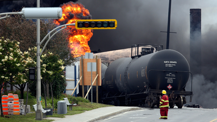 ARCHIVE PHOTO: A firefighter walks past a burning train wagon at Lac Megantic, Quebec, July 6, 2013 (Reuters / Mathieu Belanger)