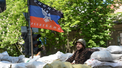 A member of the federalization supporters' self-defense movement is seen at the barricades near the flag of the Donetsk People's Republic (RIA Novosti/Mikhail Voskresenskiy)
