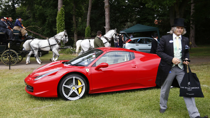 A man walks from his Ferrari as a carriage passes during the fourth day of the Royal Ascot horse racing festival at Ascot, southern England, June 21, 2013. (Reuters/Darren Staples)