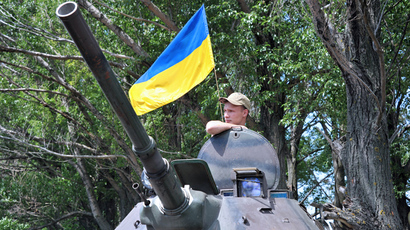A Ukrainian soldier stands guard next to an Armoured Personnel Carriers (APC) as a flag of Ukraine floats in the background, on the road from Izyum to Slavyansk on May 20, 2014 (AFP Photo)