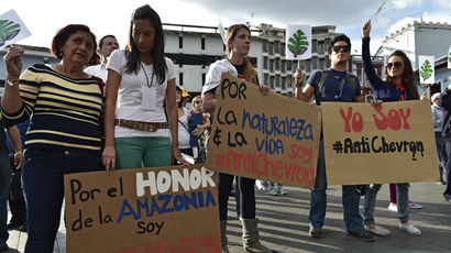 "Activists hold signs reading ""For Amazonia's honor I am AntiChevron"", ""For nature & life I am Antichevron"" and "" I am AntiChevron"" during a protest against US multinational energy corporation Chevron at a square in downtown Quito on May 21, 2014 (AFP Photo)"