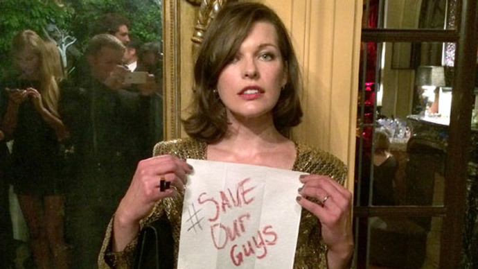 Milla Jovovich holding a sign with a hashtag #SaveOurGuys to support the Russian journos detained in Ukraine.