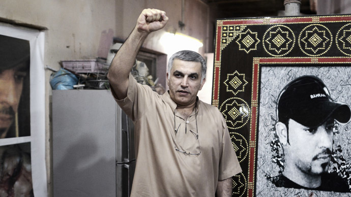 Bahraini human rights activist Nabeel Rajab (L) and Musa al-Abbar (R) stand near a portrait of Abdul Aziz al-Abbar, a Bahraini man who died from his wounds on February 23 after he was shot during clashes between police and protesters, on May 24, 2014 in the village of Sanabis, west of Manama. Rajab was recently released after 2 years in prison. (AFP Photo)