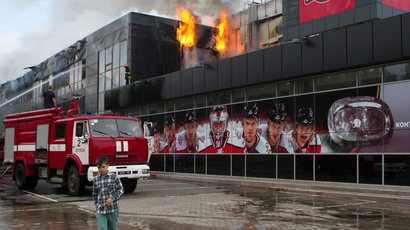 "A boy walks by as firefighters attempt to extinguish a fire at the sports arena ""Druzhba"" (Friendship), which is the home venue of the ice hockey club ""Donbass"", in Donetsk, May 27, 2014. (Reuters / Stringer)"