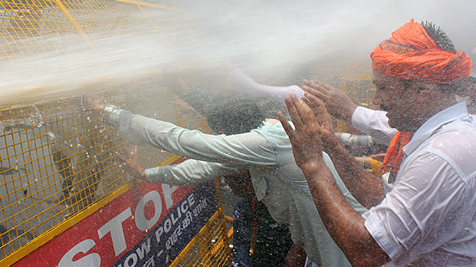 Indian Bharatiya Janata Party (BJP) demonstrators are hit by water cannon as they stand behind a police barricade during a protest against the recent gang-rape and murder of two girls, in Lucknow on June 2, 2014 (AFP Photo / STR)