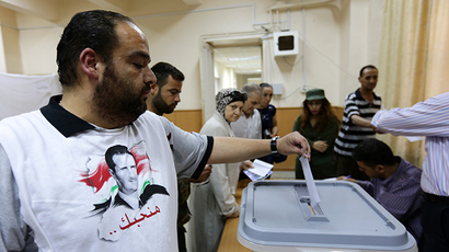 A Syrian man, wearing a shirt bearing current President Bashar al-Assad's portrait, casts his ballot as he votes in presidential election on June 3, 2014 at Bassel al-Assad school turned into a polling station in central Damascus (AFP Photo / Louai Beshara)
