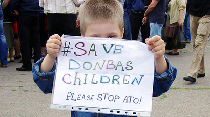 "A boy holds a placard reading ""Save Donbas children. Please stop ATO!"" (anti-terrorists operation) in the southern Ukrainian city of Odessa on June 1, 2014 (AFP Photo)"