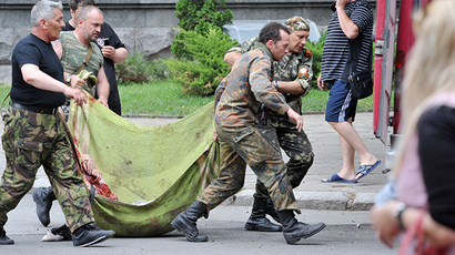 Anti-goverment militants carry the body of a fellow militant killed during an assault on a border command centre in the eastern Ukrainian city of Lugansk on June 2, 2014 (AFP Photo / Alex Inoy)