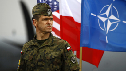 A Polish soldier stands near U.S. and Poland's national flags and a NATO flag as the first company-sized contingent of about 150 U.S. paratroopers from the U.S. Army's 173rd Infantry Brigade Combat Team based in Italy arrived to participate in training exercises with the Polish army in Swidwin, northern west Poland April 23, 2014. (Reuters/Kacper Pempel)