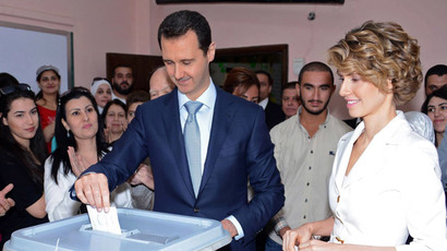 Syrian President Bashar al-Assad (C) and his wife Asma al-Assad (R) casting their votes at a polling station in Maliki, a residential area in the centre of the capital Damascus, in the country's presidential elections on June 3, 2014.(AFP Photo / HO)