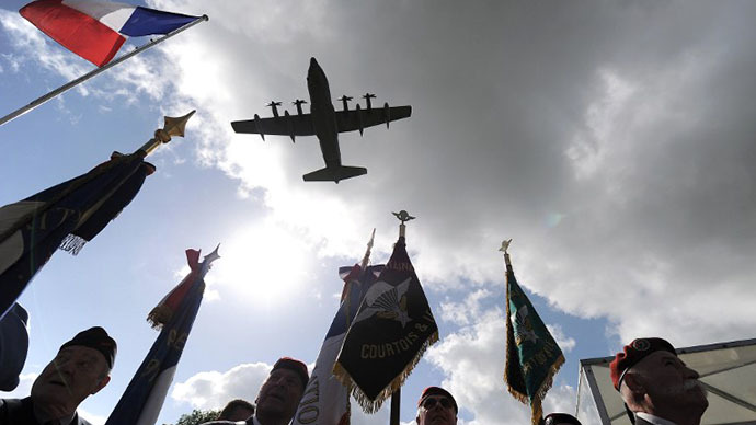A US military plane flies over a US-German D-Day commemoration ceremony in honour of airborne soldiers on June 5, 2014 in Picauville, northern France. (AFP Photo / Jean-Sebastien Evrard)