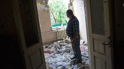 A man in one of the rooms of his house destroyed by a missile during shelling by the Ukrainian security forces in Chervoniy Molochar not far from Sloviansk. (RIA Novosti/Andrey Stenin)