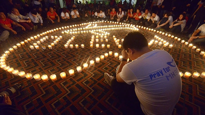 A Chinese relative of passengers on Malaysia Airlines flight MH370 prays in front of candles. (AFP Photo / Wang Zhao)