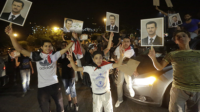 Syrians hold pictures of re-elected Syrian President Bashar al-Assad as they celebrate in Damascus after Assad was announced as the winner of the country's presidential elections on June 4, 2014. (AFP Photo / Joseph Eid)
