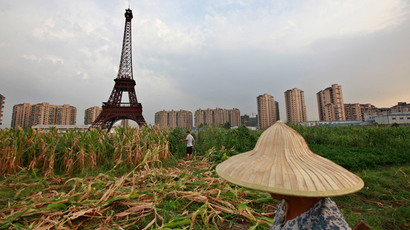 A farmer walks through a field near a replica of the Eiffel Tower at the Tianducheng development in Hangzhou, Zhejiang Province (Reuters / Aly Song)