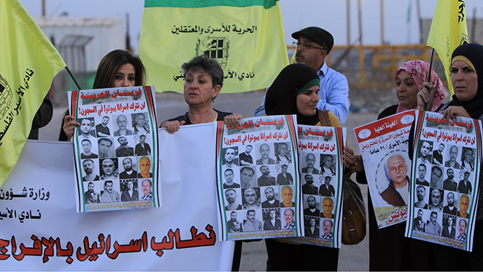 Palestinians hold pictures of detainees being held in Israeli prisons since before the 1993 Oslo peace accords as they protest against the postponement of the release of the prisoners outside the gates of Ofer prison, near the West Bank town of Betunia (AFP Photo / Abbas Momani)